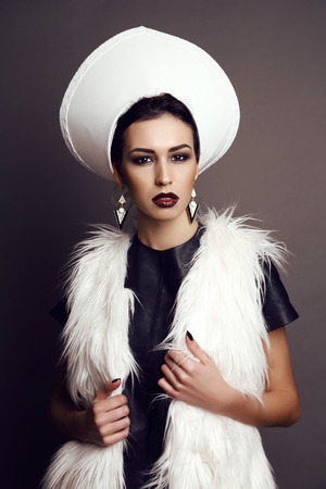 extravagant: fashion studio photo of beautiful girl with dark hair and evening makeup, in extravagant outfit