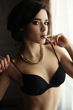 fashion photo of gorgeous woman with long hair in lingerie, smoking ciragette, posing in interior