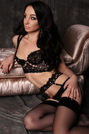 stockings woman: fashion studio photo of beautiful young woman with long dark hair and evening makeup in lingerie