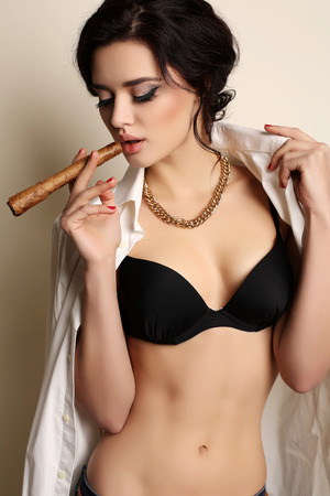 fashion studio photo of beautiful young woman with long dark hair and evening makeup smoking cigar