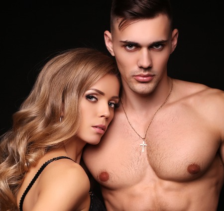 love affair: fashion studio photo of beautiful couple with sportive sexy bodies, gorgeous woman with long blond hair embracing handsome brunette man Stock Photo