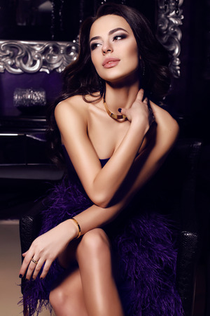 fashion interior photo of gorgeous woman with dark hair and evening makeup, wears elegant dress Stock Photo