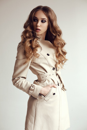 fashion photo of beautiful young woman with dark curly hair wears elegant spring coat,posing in studio Stockfoto
