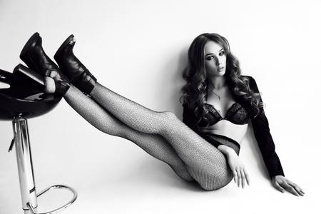 medias veladas: moda foto en blanco y negro de la mujer joven hermosa con el pelo oscuro y rizado lleva el cordón elegante de la ropa interior, medias y zapatos, que presenta en estudio