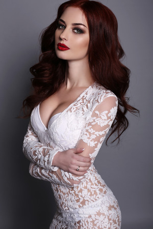 fashion studio photo of gorgeous young woman with dark hair and evening makeup, wears luxurious lace dress