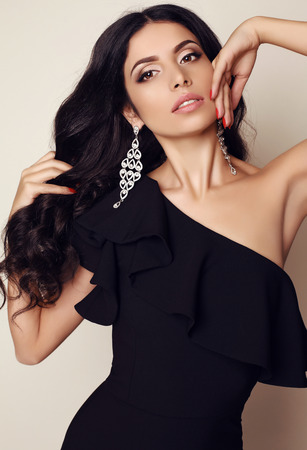 fashion photo of gorgeous woman with dark hair and evening makeup, wears elegant black dress and accessories