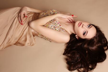 natural beauty: fashion studio photo of gorgeous young woman with dark hair and evening makeup, wears luxurious dress
