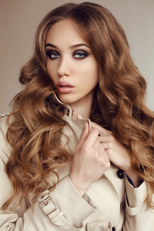 fashion studio photo of beautiful young woman with dark curly hair wears elegant spring coat