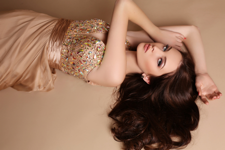 style woman: fashion studio photo of gorgeous young woman with dark hair and evening makeup, wears luxurious dress