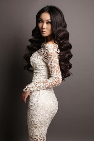 fashion studio foto van mooie sensuele Aziatische vrouw met lang donker haar in een elegante kanten jurk