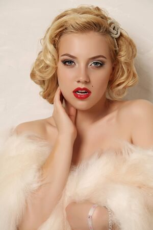 sexy fashion: fashion studio photo of gorgeous sexy woman with blond curly hair and bright makeup,wears fur Stock Photo