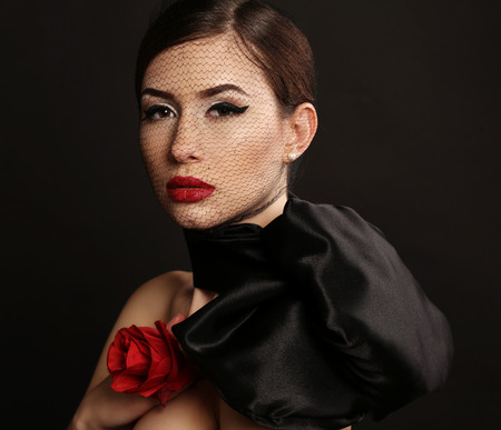 female model: fashion studio photo of gorgeous sexy woman with dark hair and bright makeup, with black veil on face and with red rose Stock Photo