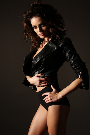 fashion studio photo of gorgeous sexy woman with dark hair and bright makeup in black lingerie and leather jacket Stock Photo
