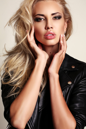 fashion studio photo of gorgeous sexy woman with blond hair and evening makeup, wears leather jacket