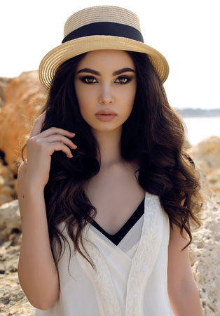 young beautiful woman: fashion outdoor photo of beautiful girl with dark hair wears casual elegant clothes and hat posing at summer seacoast