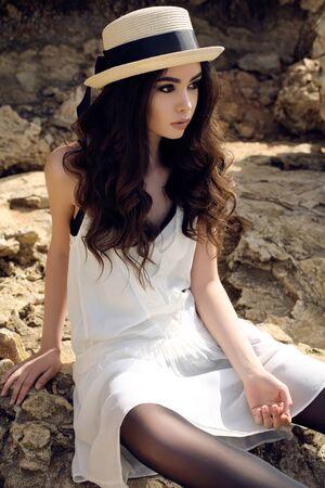 mujeres fashion: de fotografía de moda al aire libre de la muchacha hermosa con el pelo oscuro se viste con ropa casual elegante y sombrero en la costa del verano Foto de archivo
