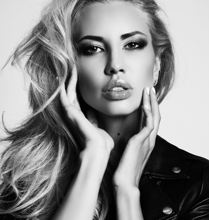 hair studio: fashion studio photo of gorgeous sexy woman with blond hair and evening makeup, wears leather jacket