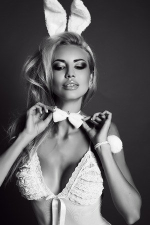fashion studio black and white photo of gorgeous sexy woman with blond hair in lingerie dress, with bunny ears headband