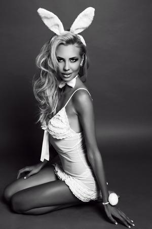 studio de mode photo noir et blanc de belle femme sexy avec les cheveux blonds en robe de lingerie, avec des oreilles de lapin bandeau