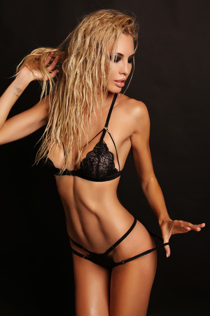 sensual woman: fashion studio photo of gorgeous sexy woman with blond hair wears luxurious lace black lingerie Stock Photo