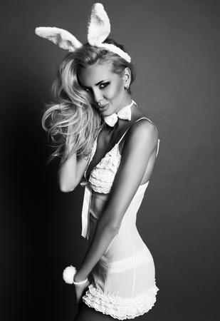 Studio moda foto in bianco e nero della donna splendida sexy con i capelli biondi in abito lingerie, con coniglietto orecchie archetto Archivio Fotografico