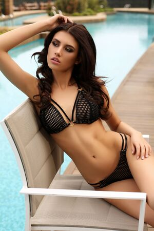 sexy model: fashion summer outdoor photo of gorgeous woman with dark hair in luxurious swimsuit posing beside swimming pool