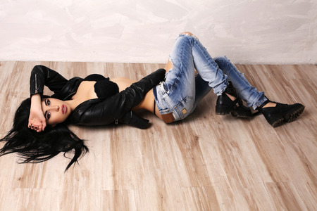 fashion studio photo of gorgeous sexy woman with dark hair in lingerie and jeans lying on wood floor