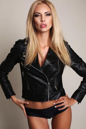 jacket: foto de estudio de moda de la mujer atractiva hermosa con el pelo rubio en ropa interior y chaqueta de cuero Foto de archivo