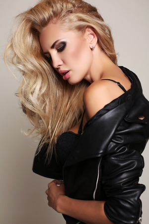 fashion studio photo of gorgeous sexy woman with blond hair in lingerie and leather jacket