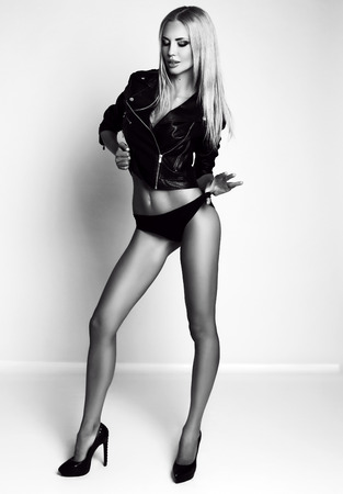sexy fashion: fashion black and white studio photo of gorgeous sexy woman with blond hair in lingerie and leather jacket Stock Photo