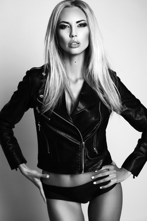 fashion black and white studio photo of gorgeous sexy woman with blond hair in lingerie and leather jacket Stock Photo