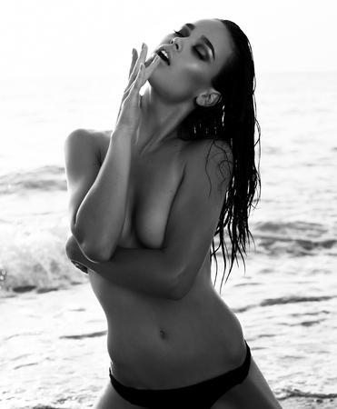 girls in bikini: fashion summer outdoor black and white photo of gorgeous sexy girl with dark hair posing on beach