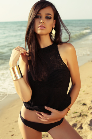 fashion summer outdoor photo of gorgeous girl with dark hair posing on beach