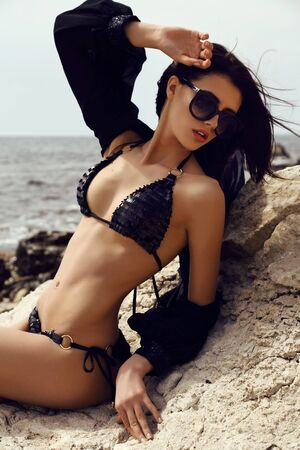 sexy model: fashion summer outdoor photo of gorgeous woman with dark hair in elegant swimsuit and sunglasses posing on sea coast Stock Photo