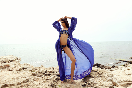 fashion summer outdoor photo of gorgeous woman with dark hair in elegant swimsuit posing on sea coast Stock Photo