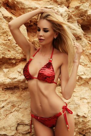 blonde bikini: fashion summer outdoor photo of gorgeous woman with blond hair in elegant swimsuit  posing on sea coast