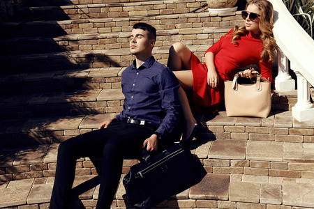 fashion photo of beautiful couple in elegant clothes with bags posing on stairs