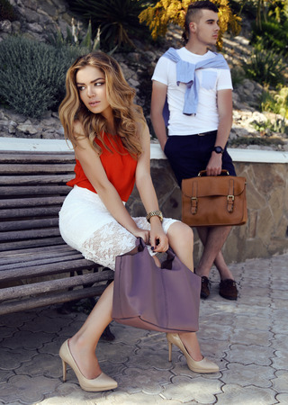 fashion photo of beautiful couple in elegant clothes with bags posing in summer park Stock Photo - 59120234