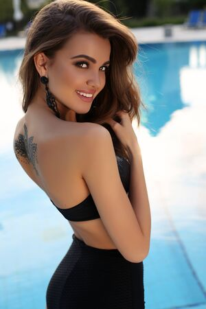 sensual woman: fashion outdoor photo of gorgeous sensual woman with dark hair in elegant swimsuit posing beside swimming pool Stock Photo