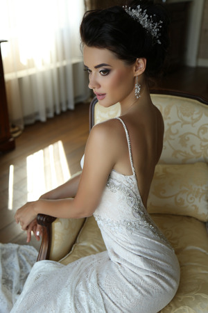 sexy bride: fashion interior photo of gorgeous bride in luxurious wedding dress posing at bedroom Stock Photo
