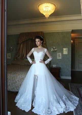 luxurious: fashion interior photo of gorgeous bride in luxurious wedding dress posing at bedroom Stock Photo