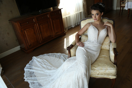 fashion interior photo of gorgeous bride in luxurious wedding dress posing at bedroom 스톡 콘텐츠