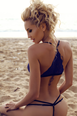 cabello rizado: fashion outdoor photo of gorgeous sexy woman with blond curly hair in elegant lingerie posing at summer beach