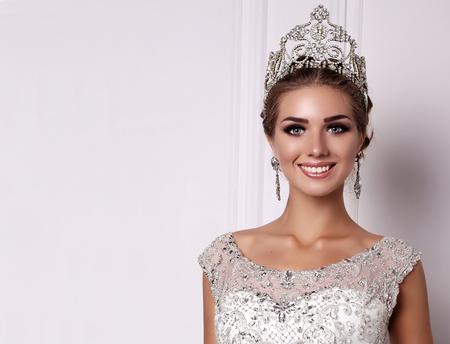 豪華なウェディング ドレスと貴重な王冠の黒い髪とゴージャスな女性のファッション スタジオ写真