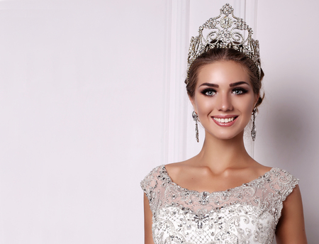 fashion studio photo of gorgeous woman with dark hair in luxurious wedding dress and precious crown