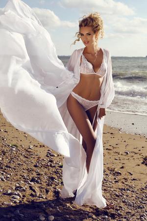 moda foto all'aperto di splendida donna sexy con capelli ricci biondi in elegante lingerie di pizzo posa in spiaggia estate