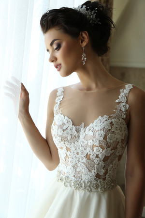luxurious: fashion interior photo of gorgeous bride in luxurious wedding dress posing in hotels bedroom