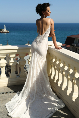 sexy bride: fashion interior photo of gorgeous bride in luxurious wedding dress posing at balcony with sea view