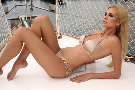 fashion outdoor photo of gorgeous sexy woman with blond hair in elegant swimsuit posing on yacht
