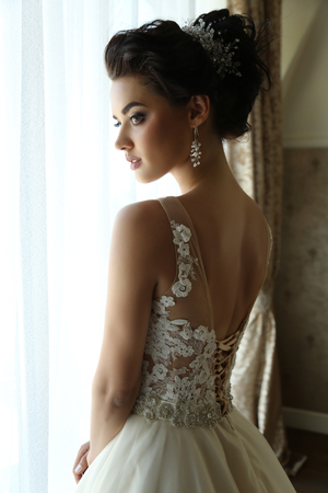 fashion interior photo of gorgeous bride in luxurious wedding dress posing in hotels bedroom